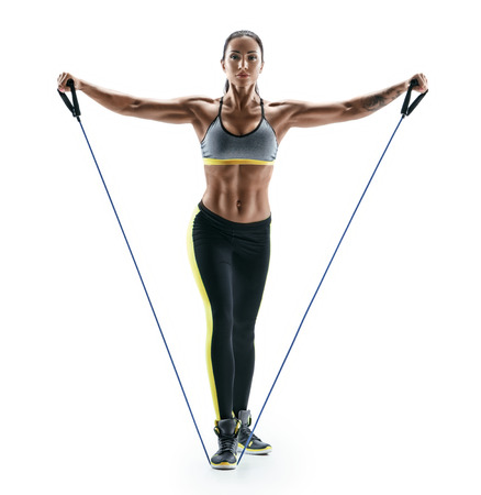 Attractive muscular woman performs exercises for deltoid muscles using an resistance bands. Photo of young brunette isolated on white background. Strength and motivation