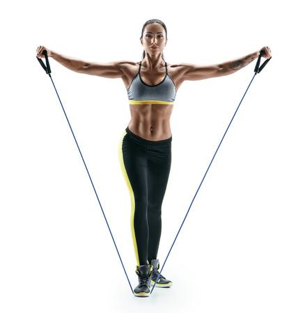 Attraktive muskulöse Frau führt Übungen für Deltoidmuskeln unter Verwendung eines Widerstandbandes durch. Foto des jungen Brunette getrennt auf weißem Hintergrund. Stärke und Motivation