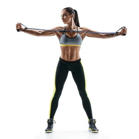 美しい強力なモデルは、抵抗バンドを使用して、胸の筋肉のための演習を行います。白い背景で隔離の若い女性の写真。強さと動機。