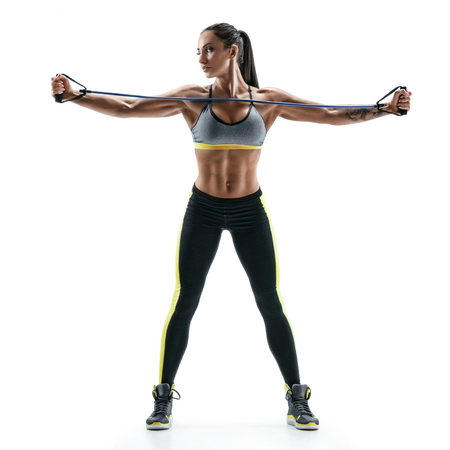 Beautiful strong model performs exercises for the muscles of the chest using an  resistance bands. Photo of young woman isolated on white background. Strength and motivation.