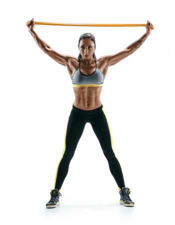 Jong meisje voert oefeningen voor de spieren van de rug en handen met behulp van een weerstand band en kijken naar de camera. Foto van atletisch meisje dat op witte achtergrond wordt geïsoleerd. Kracht en motivatie.