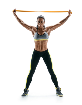 Young girl performs exercises for the muscles of the back and hands using a resistance band and looking at the camera. Photo of athletic girl isolated on white background. Strength and motivation.
