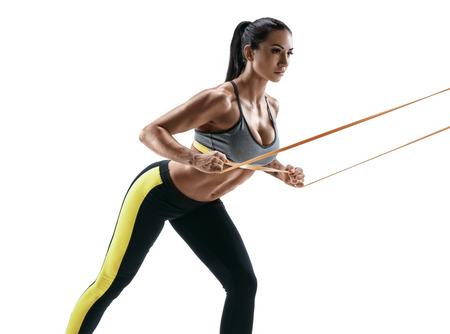 Mooie atletische vrouw tijdens training met opschortingsriemen. De jonge vrouw voert geschiktheidsoefeningen op witte achtergrond uit. Kracht en motivatie