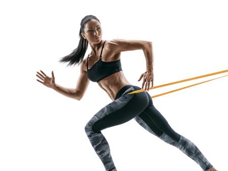 Mulher forte usando uma banda de resistência em sua rotina de exercícios. A jovem mulher executa exercícios da aptidão no fundo branco. Foto de archivo