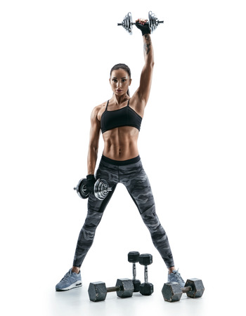 Attractive muscular woman lifting heavy dumbbells on white background. Strength and motivation.