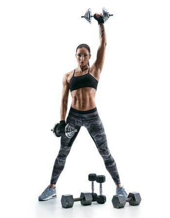 Mujer muscular atractiva que levanta pesas de gimnasia pesadas en el fondo blanco. Fuerza y ??motivación Foto de archivo - 76753279