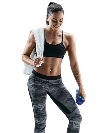 Resting time. Attractive smiling woman with towel on shoulders holding bottle of water. Health concept. Standard-Bild