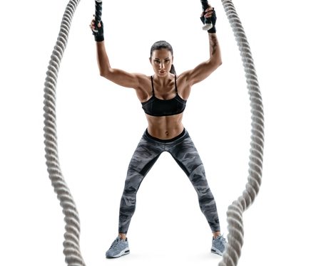 Athletic woman working with heavy ropes. Photo of attractive brunette in sportswear isolated on white background. Strength and motivation.