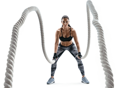 Strong woman working with heavy ropes. Photo of sporty girl in sportswear isolated on white background. Strength and motivation. Stockfoto