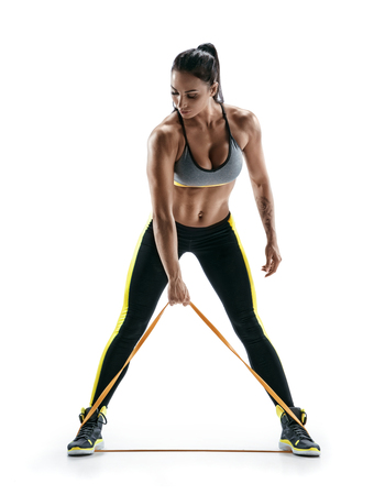 Woman with beautiful athletic body performs exercises using a resistance band. Photo of young woman isolated on white background. Strength and motivation. Standard-Bild