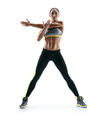 Strong girl with perfect body performs fitness exercises on white background. Strength and motivation