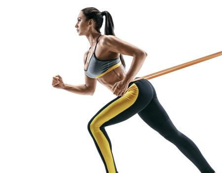 Aantrekkelijk sportief meisje tijdens training met opschortingsriemen die op witte achtergrond worden geïsoleerd. Kracht en motivatie Stockfoto