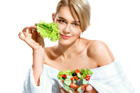 Charming young woman with lettuce leaf. Photo of smiling blonde in bathrobe holding vegetable salad isolated on white background. Healthy lifestyle Stock Photo