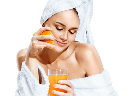 Happy girl with an orange slice and glass of juice. Photo of girl after bath in bathrobe and towel on her head isolated on white background. Diet. Healthy lifestyle