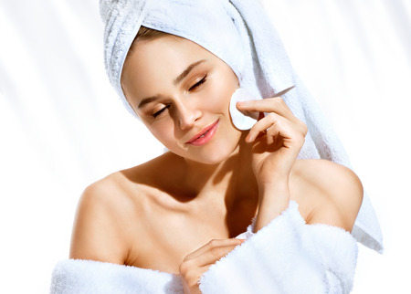 Charming lady removes makeup from her delicate skin of her face with a cotton swab. Photo of girl after bath isolated on white background. Skin care and beauty