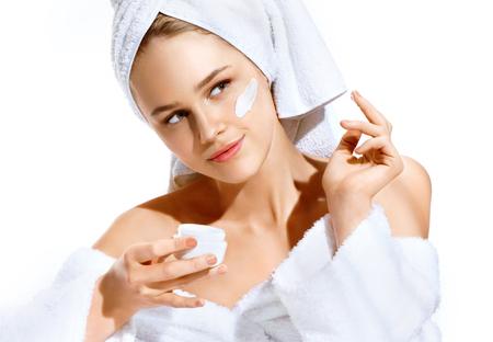 Appliquer une crème hydratante. Sexy jeune mannequin après le bain se soucie de son visage. Photo de femme avec une peau parfaite. Concept de soins de la peau Banque d'images - 76975310
