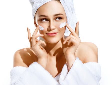 Dazzling young woman applying moisturizing cream on her face. Photo of woman in white bathrobe and towel on white background. Skin care concept Stock fotó