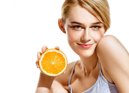 Smiling young girl holding oranges halves on white background. Great food for healthy lifestyle 스톡 콘텐츠