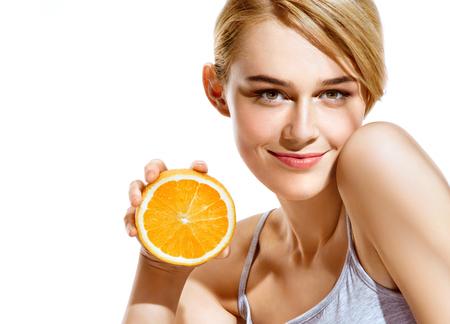 Glimlachend jong meisje dat sinaasappelen helften op een witte achtergrond. Lekker eten voor een gezonde levensstijl Stockfoto