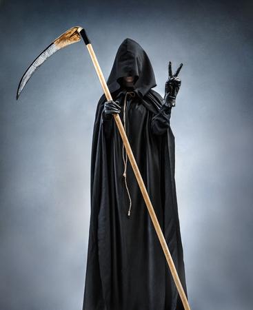 死神は勝利のサインを示します。勝利ジェスチャまたは 2 本の指を示すシルエット死神の写真。死 写真素材