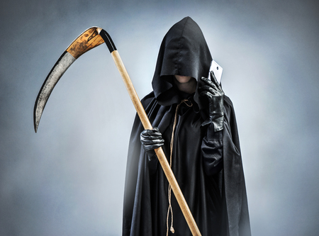 Grim Reaper making a phone call. Photo of silhouette grim reaper with smartphone. Death Stock Photo