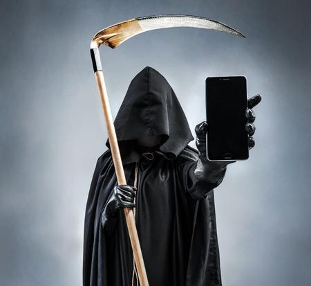 Bild des Sensenmanns, der schwarzes Handy mit leerem schwarzem Schirm hält und zeigt. Foto der Silhouette Sensenmann mit Smartphone. Tod