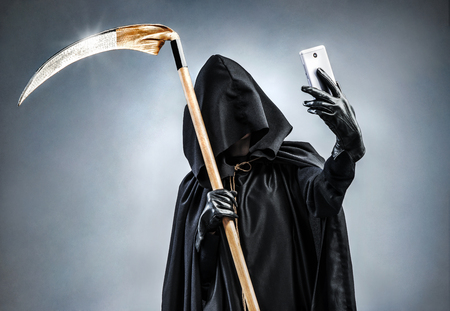 Grim Reaper making selfie photo on smartphone. Photo of personification of death wielding a large scythe in silhouette. Archivio Fotografico
