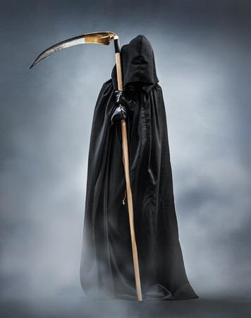 Sensenmann, der nachts im Nebel steht. Foto der Verkörperung des Todes, der eine große Sense im Schatten ausübt.