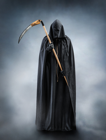 Grim Reaper standing in the fog at night. Photo of personification of death wielding a large scythe in silhouette. Stock Photo