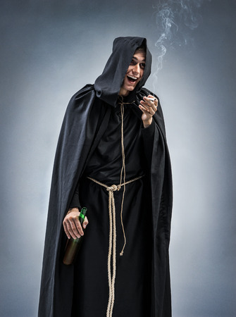 Cheerful Catholic monk smokes and drinks wine. Photo of a drunken monk on gray background. Religious concept