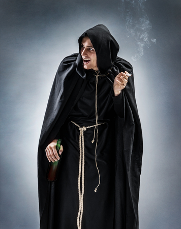 Young monk with bottle of wine and cigarette. Photo of a drunken monk on gray background. Religious concept Фото со стока