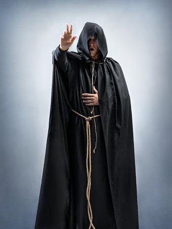 修道士の説教か、祈りを読み取ります。修道士のローブを身に着けている人の肖像画。完全な高さ。信仰、精神性および宗教のためのコンセプト
