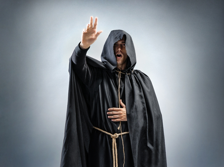 カトリック修道僧の説教です。修道士のローブを身に着けている男の写真。信仰、精神性および宗教のためのコンセプト