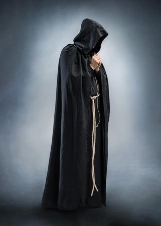 祈り僧侶、祈りの折られた手のシルエット。祈りでモンクの写真。完全な高さ。信仰、精神性および宗教のためのコンセプト
