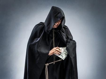 僧侶は、宗教、不正直な方法で稼いでいます。貪欲の修道士が彼のポケットにお金を隠しての写真。宗教的な概念 写真素材