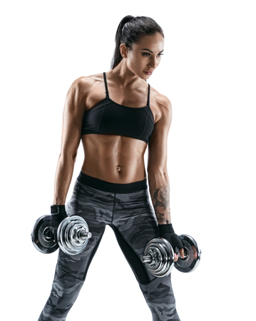 Young girl doing exercise with dumbbell as part of fitness workout. Photo of muscular girl isolated on white background. Strength and motivation