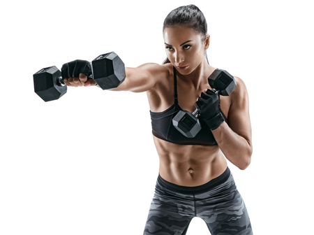 Sporty woman doing boxing exercises, making direct hit with dumbbells. Photo of muscular female wearing sportswear on white background. Strength and motivation