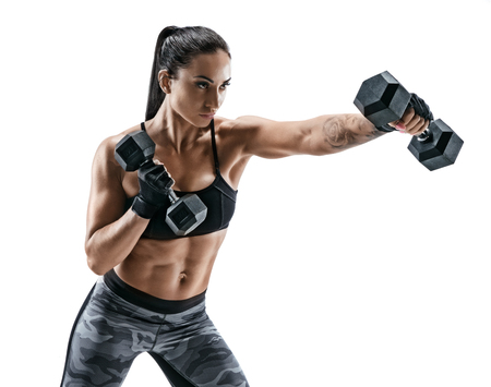 Strong woman doing boxing exercises making direct hit with dumbbells. Photo of sporty muscular female wearing sportswear on white background. Strength and motivation Banco de Imagens