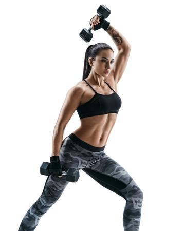 Atletische vrouw die spieren met domoren pompen. Foto van sportief spierwijfje in sportkleding op witte achtergrond. Kracht en motivatie