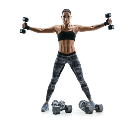 Fitness model exercising with dumbbells in both hands. Photo of muscular woman isolated on white background. Strength and motivation. Stockfoto