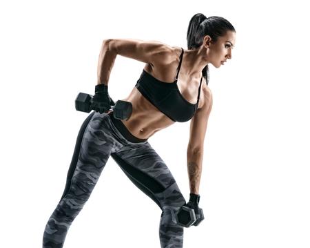 フィットネス女性は腕の運動を行います。白い背景にダンベルでワークアウト筋肉女性の写真。強度とモチベーション