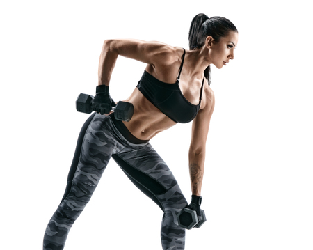 Fitness woman doing exercise for arms. Photo of muscular woman working out with dumbbells on white background. Strength and motivation