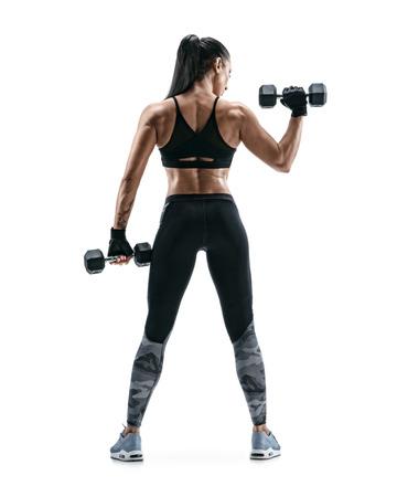 Donna forte che lavora con i manubri, flettendo il braccio. Foto della donna sportiva in abiti sportivi su fondo bianco. Retrovisore. Lunghezza intera