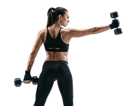 ダンベルを持つ強い女性。白い背景の上のスポーツ ウエアでスポーティな女性の写真。背面図