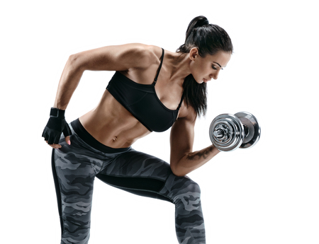 Young muscular woman doing heavy dumbbell exercise for biceps. Photo of fitness model working out with dumbbells on white background. Strength and motivation