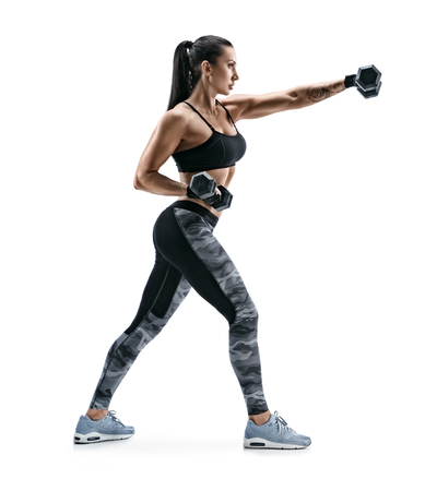 Sporty girl during boxing exercise making direct hit with dumbbells. Photo of strong girl on white background. Strength and motivation. Side view