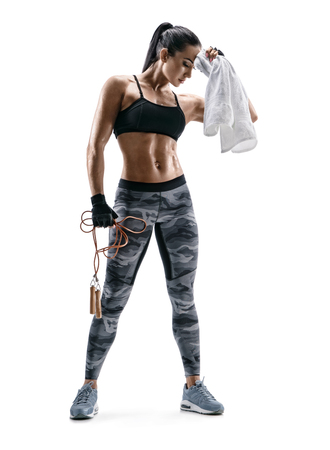 Fitness girl is resting. Sporty girl with skipping rope and towel in hands on white background. Strength and motivation