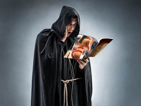 Monk in perplexity, reading an erotic magazine.