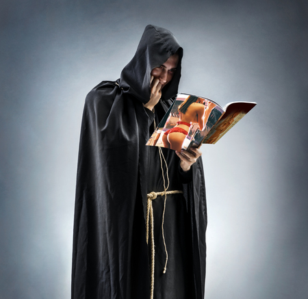 The monk reads the erotic magazine with enthusiasm. Imagens - 79070693