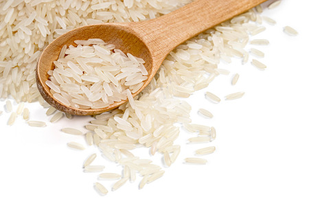 Long parboiled rice with wooden spoon scattered on white background. Close up, top view, high resolution product. Copy space. Healthy food concept